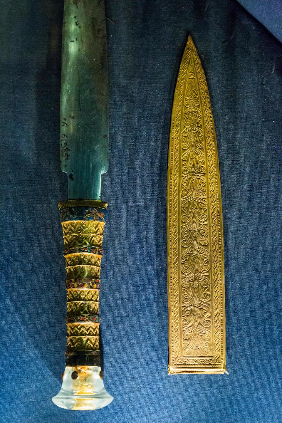 An ancient dagger with a hilt and sheath made of gold