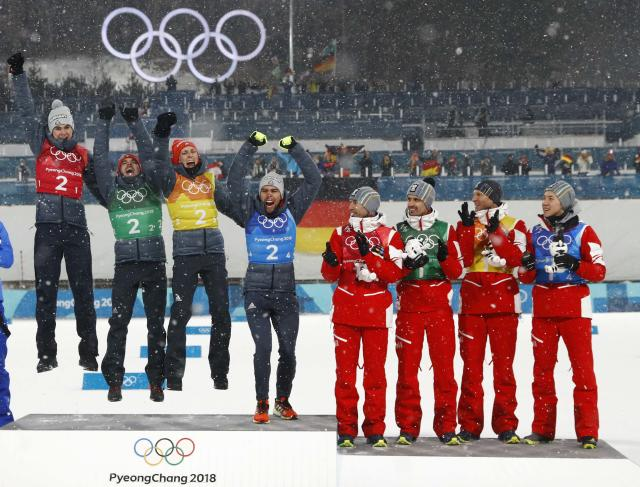 Nordic Combined Events - Pyeongchang 2018 Winter Olympics - Men's Team 4 x 5 km Final - Alpensia Cross-Country Skiing Centre - Pyeongchang, South Korea - February 22, 2018 - Gold medallists Vinzenz Geiger, Fabian Riessle, Eric Frenzel and Johannes Rydzek of Germany celebrate next to bronze medallists Austria during the victory ceremony. REUTERS/Kai Pfaffenbach
