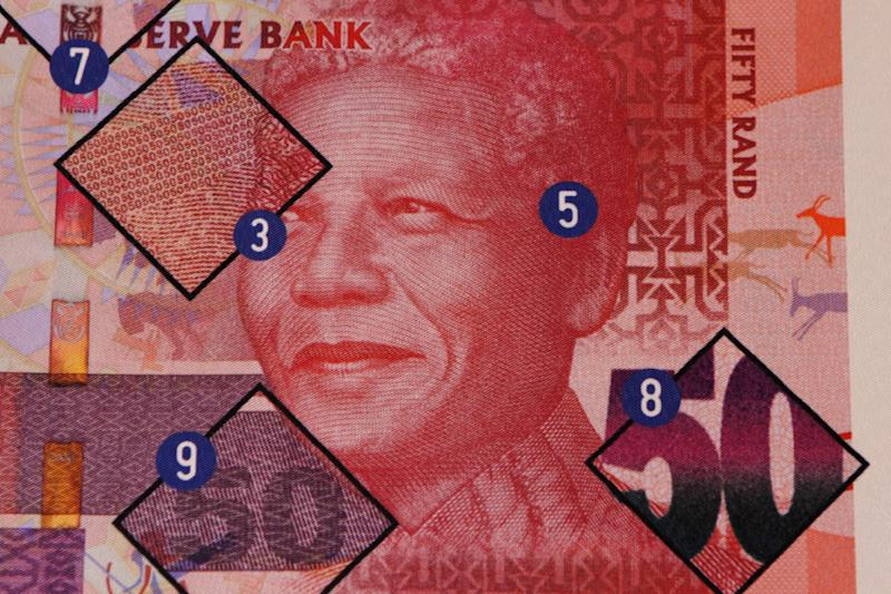 A poster showing safety features of a bank note bearing the image of former president Nelson Mandela, at a press launch, in Pretoria, South Africa, Tuesday, Nov. 6, 2012.  New South African banknotes featuring the image of former president and anti-apartheid icon Nelson Mandela are going into circulation.  Reserve bank governor Gill Marcus made the first purchase using the new rand notes at a small shop in Pretoria Tuesday. She says the country tries to upgrade its notes every seven years for security reasons as technologies change.  (AP Photo/Denis Farrell)
