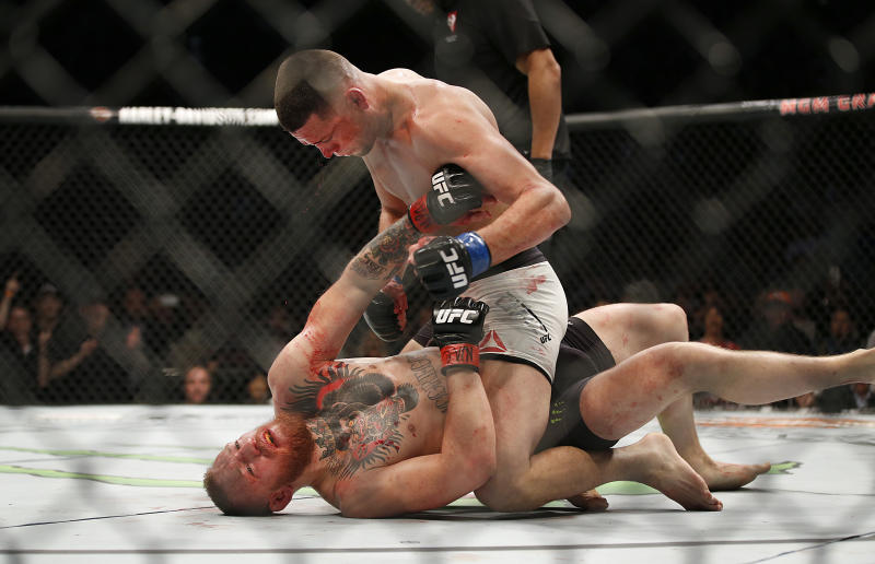 Nate Diaz, top, trades punches Conor McGregor during their UFC 196 welterweight mixed martial arts match Saturday, March 5, 2016, in Las Vegas. (AP Photo/Eric Jamison)