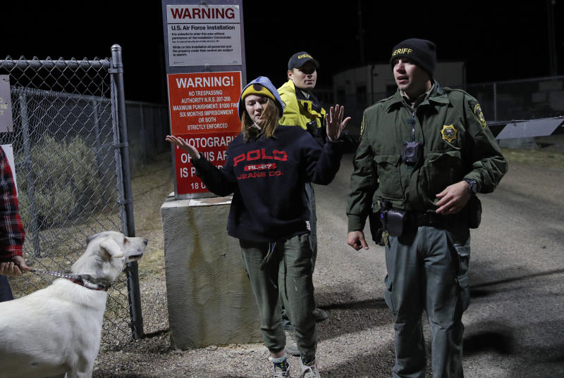 "Sheriff's deputies escort a woman who ducked under the gate at an entrance to the Nevada Test and Training Range near Area 51, Sept. 20, 2019, near Rachel, Nev. People gathered at the gate inspired by the ""Storm Area 51"" internet hoax. (Photo: John Locher/AP)"