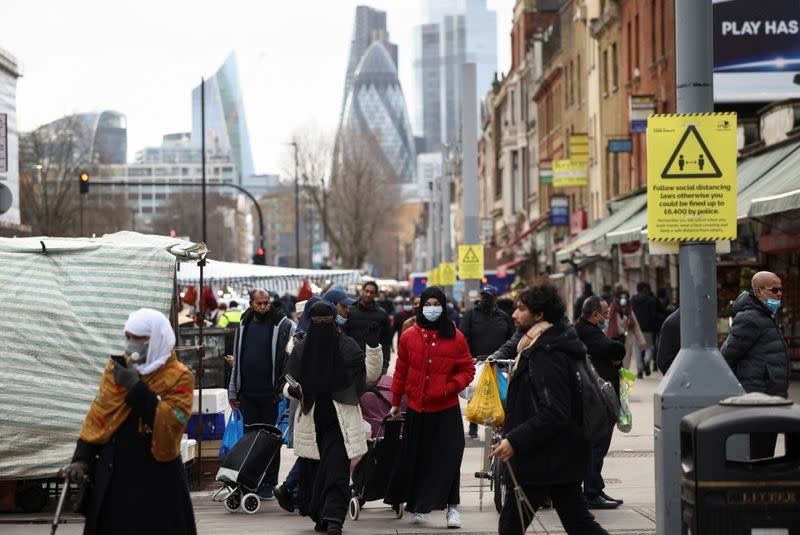 People walk past shops and market stalls, amid the coronavirus disease (COVID-19) outbreak in London