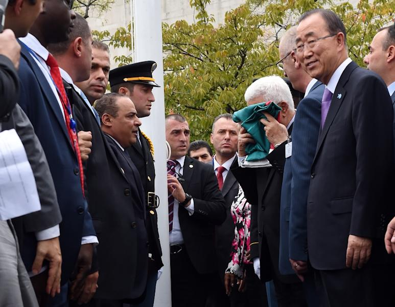 Palestinian president Mahmud Abbas kisses the Palestinian flag as Secretary General Ban Ki-moon looks during the flag raising ceremony at the UN in New York on September 30, 2015 (AFP Photo/Timothy A. Clary)