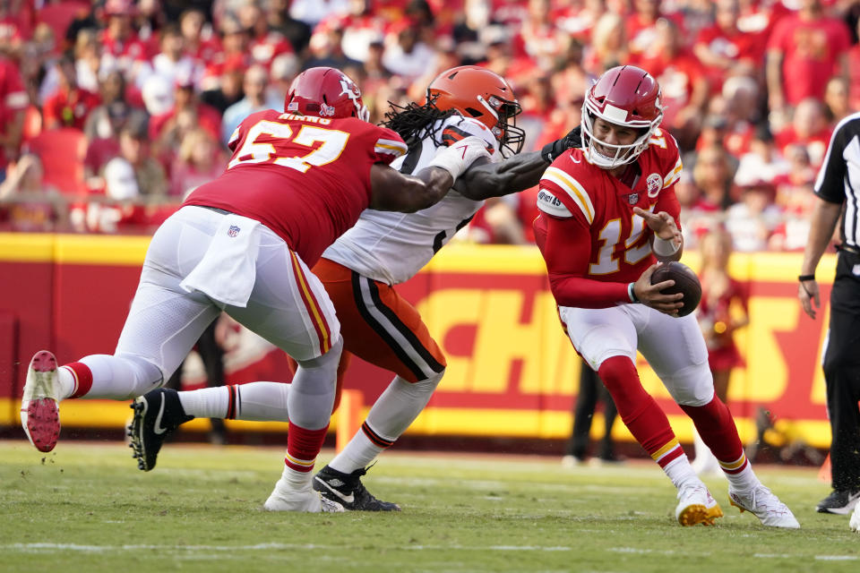 Kansas City Chiefs quarterback Patrick Mahomes, right, slips away from Cleveland Browns defensive end Jadeveon Clowney as Chiefs offensive tackle Lucas Niang (67) blocks during the second half of an NFL football game Sunday, Sept. 12, 2021, in Kansas City, Mo. (AP Photo/Ed Zurga)