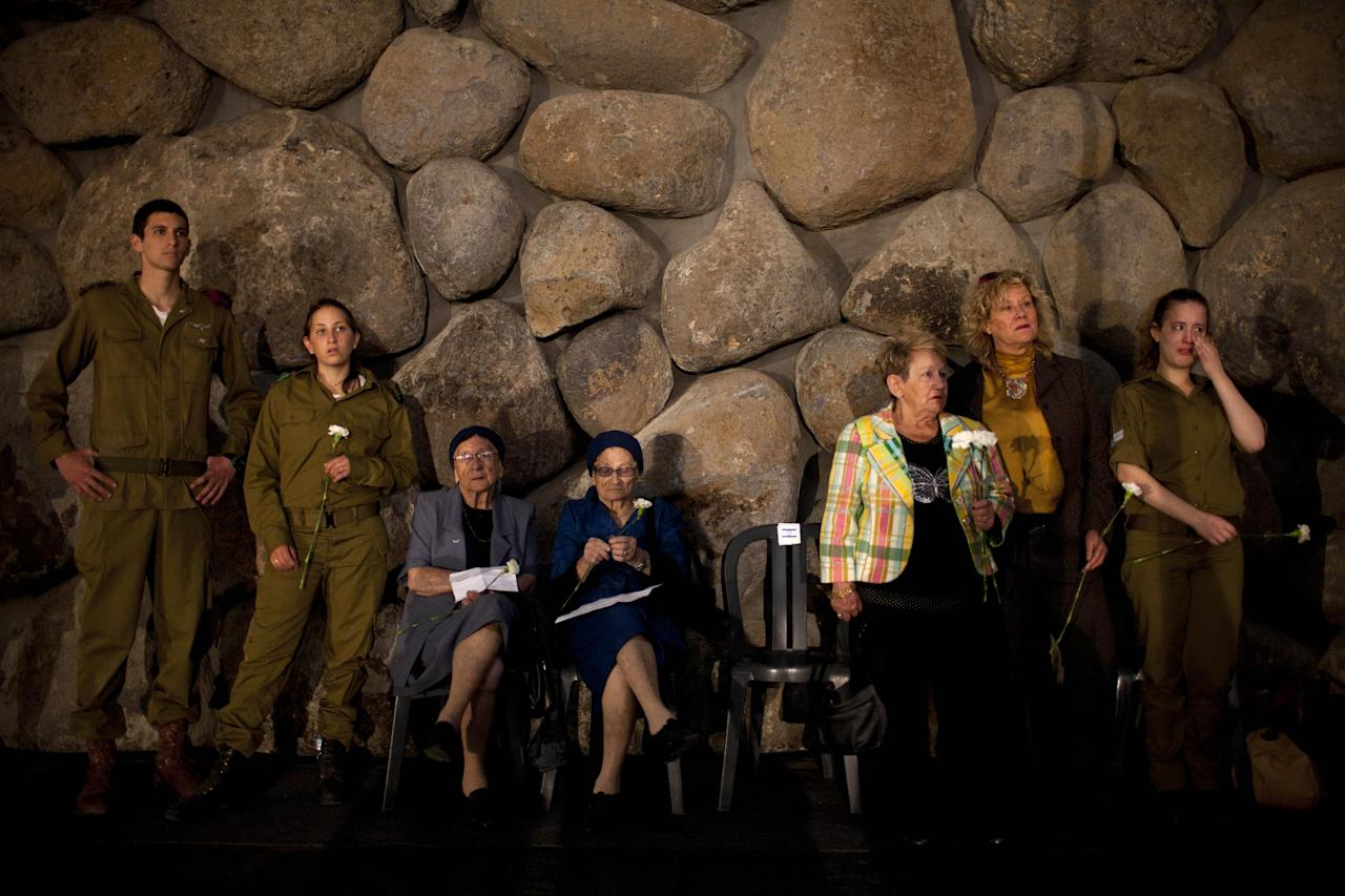 Holocaust survivors and their relatives hold flowers during a ceremony marking the annual Holocaust Remembrance Day at the Yad Vashem Holocaust Memorial in Jerusalem, Monday, April 8, 2013. Israel came to a standstill for two mournful minutes Monday as sirens pierced the air in an annual ritual to remember the 6 million Jews systematically murdered by German Nazis and their collaborators during the Holocaust in World War II. (AP Photo/Oded Balilty)