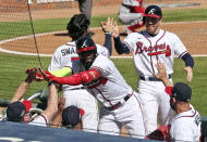 Atlanta Braves' Marcell Ozuna, center, is greeted at the dugout after hitting a two-run home run in the eighth inning against the Cincinnati Reds in Game 2 of a National League wild-card baseball series, Thursday, Oct. 1, 2020, in Atlanta. (Curtis Compton/Atlanta Journal-Constitution via AP)