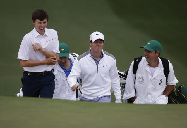 Matthew Fitzpatrick, left, of England, walks with Rory McIlroy, of Northern Ireland, and their caddies to the seventh green during a practice round for the Masters golf tournament Tuesday, April 8, 2014, in Augusta, Ga. (AP Photo/Darron Cummings)