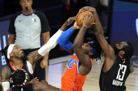 Oklahoma City Thunder's Luguentz Dort (5) goes up for a shot as Houston Rockets' James Harden (13) and Robert Covington, left, defend during the second half of an NBA basketball first round playoff game Saturday, Aug. 29, 2020, in Lake Buena Vista, Fla. (AP Photo/Ashley Landis)