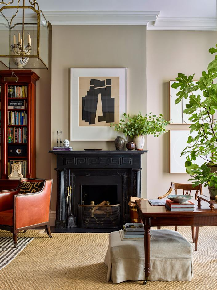 """<div class=""""caption""""> A custom scagliola mantel designed by Schafer and fabricated by plaster artisan Ahmad Suleiman dominates a light-filled corner of the living room. The artwork is by Jack Sonenberg. An antique dining table purchased in Bath, England, serves as a desk for post-office late-night work; it's paired with a 19th-century leather and wood library chair. </div>"""