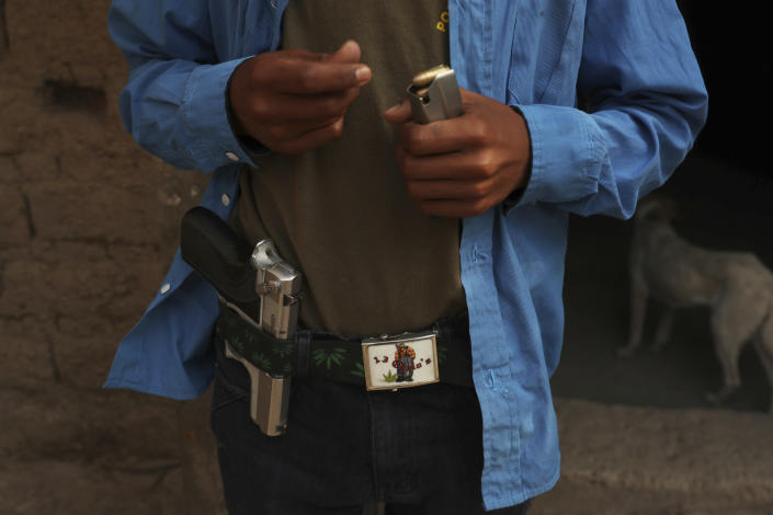 Luis Gustavo Morales loads a bullet into a clip at his home in Ayahualtempa, Guerrero state, Mexico, Wednesday, April 28, 2021. The 15-year-old, who says he always carries the pistol, is the only boy who joins his father every 16 days for shifts to guard their town's entrance. (AP Photo/Marco Ugarte)