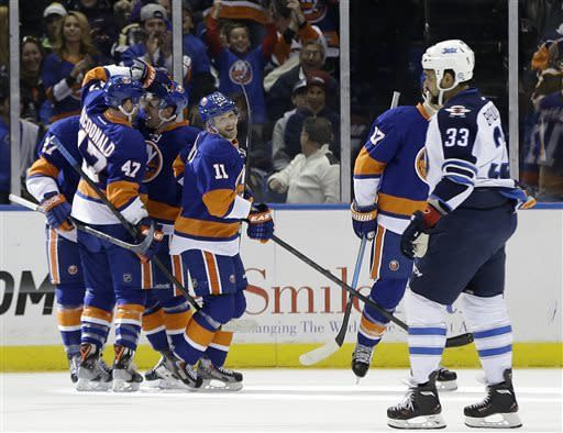 Islanders teammates celebrate with center Anders Lee (27), center of scrum, after he scored his first NHL goal in the first period of their NHL hockey game as Winnipeg Jets' Dustin Byfuglien skates past at Nassau Coliseum in Uniondale, N.Y., Tuesday, April 2, 2013. (AP Photo/Kathy Willens)
