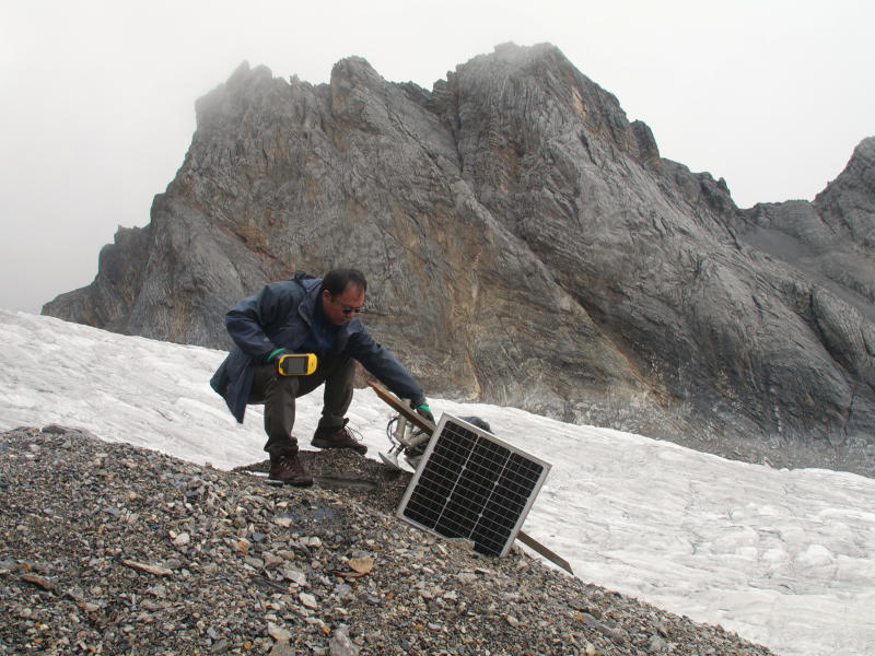 This Sept. 22, 2018 photo shows glaciologist Wang Shijin repairing a broken remote meteorological station on the Baishui Glacier No. 1 on the Jade Dragon Snow Mountain in the southern province of Yunnan in China. Scientists say the glacier is one of the fastest melting glaciers in the world due to climate change and its relative proximity to the Equator. It has lost 60 percent of its mass and shrunk 250 meters since 1982. (AP Photo/Sam McNeil)