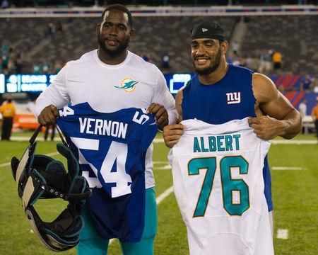 Aug 12, 2016; East Rutherford, NJ, USA; Miami Dolphins offensive tackle Branden Albert (76) and New York Giants defensive end Olivier Vernon (54) after the game f at MetLife Stadium. The Miami Dolphins defeat the New York Giants 27-10. Mandatory Credit: William Hauser-USA TODAY Sports / Reuters Picture Supplied by Action Images