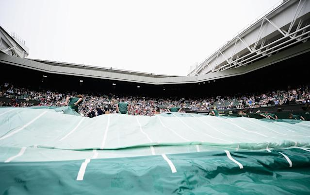 LONDON, ENGLAND - JUNE 27: Ground staff pull the rain covers across Centre Court as rain interrupts play during the Ladies' Singles second round match between Agnieszka Radwanska of Poland and Mathilde Johansson of France on day four of the Wimbledon Lawn Tennis Championships at the All England Lawn Tennis and Croquet Club on June 27, 2013 in London, England. (Photo by Dennis Grombkowski/Getty Images)