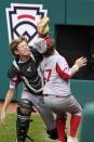 Sioux Falls, S.D. catcher Easton Riley, left, collides with Sioux Falls, S.D.'s Noah Kuenzi (17) after making the catch on a foul ball hit by Hamilton, Ohio's Chance Retherford (18) during the second inning of a baseball game at the Little League World Series in South Williamsport, Pa., Saturday, Aug. 28, 2021. (AP Photo/Gene J. Puskar)