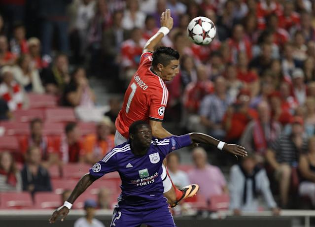Benfica's Oscar Cardozo, top jumps above Anderlecht's Fabrice N'Sakala during the Champions League group C soccer match between Benfica and Anderlecht Tuesday, Sept. 17, 2013, at Benfica's Luz stadium in Lisbon. (AP Photo/Armando Franca)