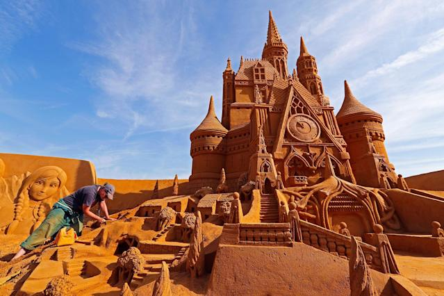 "<p>Sand carver Susanne Paucker from Germany works on a sculpture during the Sand Sculpture Festival ""Disney Sand Magic"" in Ostend, Belgium June 22, 2017. (Yves Herman/Reuters) </p>"