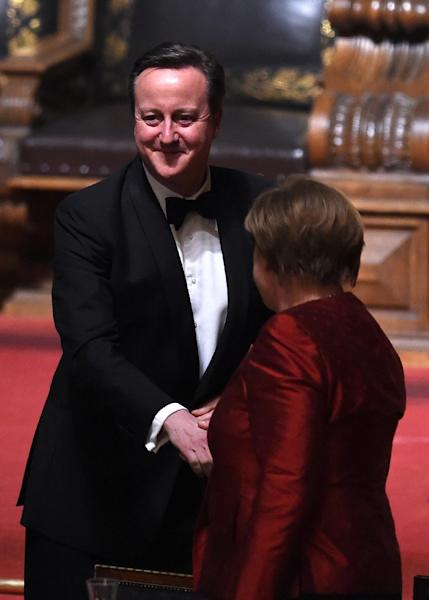 German Chancellor Angela Merkel (R) shakes hands with British Prime Minister David Cameron after his speech at the Matthiae-Mahr Dinner in Hamburg, on February 12, 2016 (AFP Photo/Carmen Jaspersen)