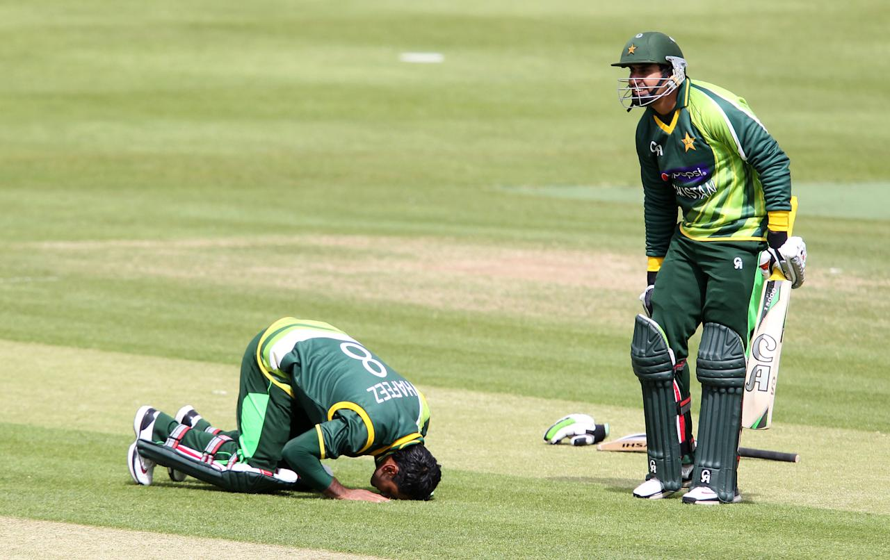 Pakistan's Mohammad Hafeez (L) reacts after reaching his century as team-mate Nasir Jamshed (R) looks on during the One Day International (ODI) cricket match between Pakistan and Ireland at Clontarf Cricket Club in Dublin on May 23, 2013.