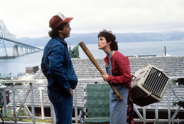 Steve Guttenberg standing in front of Ally Sheedy while she threatens him with a bat in a scene from the film 'Short Circuit', 1986. (Photo by David Foster Productions/Getty Images)