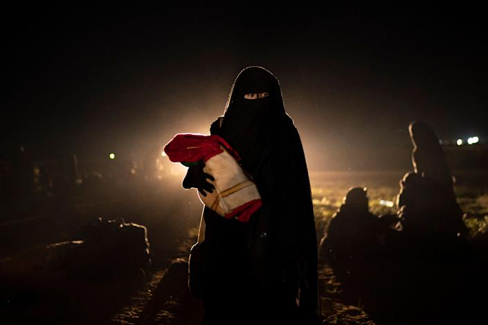 A woman who was evacuated out of the last territory held by Islamic State militants holds her baby after being screened by U.S.-backed Syrian Democratic Forces (SDF) in the desert outside Baghouz, Syria, Monday, February 25, 2019.