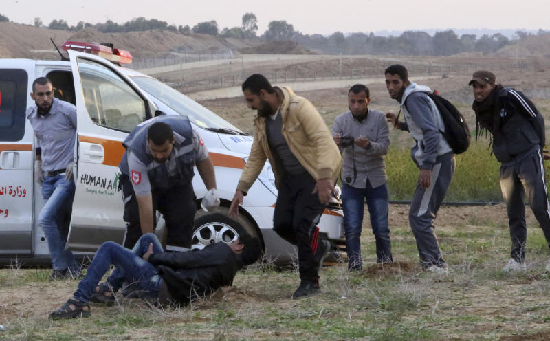 Medics and protesters run to evacuate a wounded youth from near the fence of the Gaza Strip border with Israel during a protest east of Gaza City, Friday, Nov. 16, 2018. (AP Photo/Adel Hana)