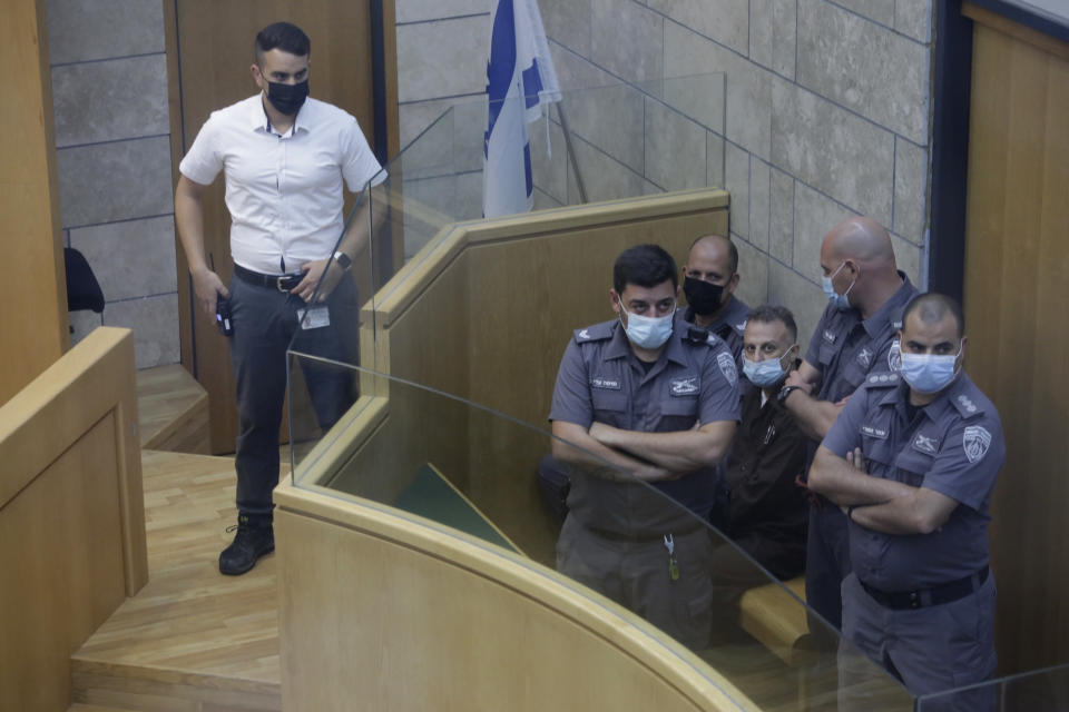 Yakub Kadari is surrounded by guards in a courtroom in Nazareth, Israel, after he and three other Palestinian fugitives were captured on Saturday, Sept. 11, 2021. Israeli police on Saturday said they have arrested four of the six Palestinians who broke out of a maximum-security prison this week — including a famed militant leader whose exploits over the years have made him a well-known figure in Israel. (AP Photo/Sebastian Scheiner)