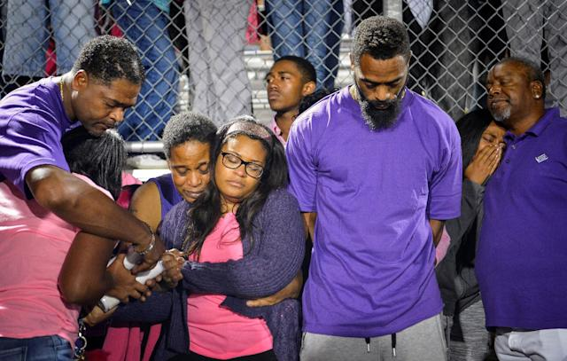 Shoshana Boyd (center L) and Olympic sprinter Tyson Gay (center R) stand surrounded by family and friends during a candlelight vigil at Lafayette High School for their daughter Trinity Gay, who died in an exchange of gunfire early Sunday morning, in Lexington, Kentucky October 17, 2016. REUTERS/Bryan Woolston TPX IMAGES OF THE DAY