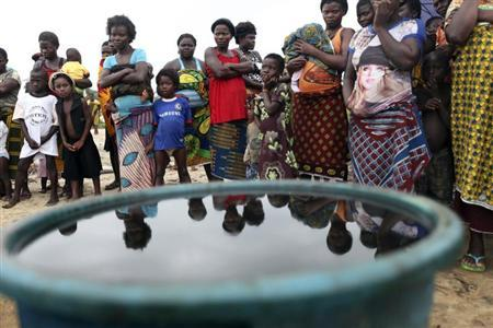 Villagers stand near a container containing crude oil collected by villagers as sample at the shore of the Atlantic ocean, days after Royal Dutch Shell's Bonga off-shore oil spill, in Nigeria's delta state