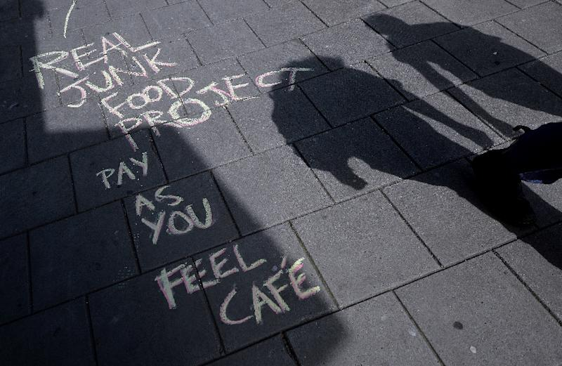 Chalked words on a pavement point to a Real Junk Food Project (RJFP) cafe in Brighton, southeast England (AFP Photo/Glyn Kirk)