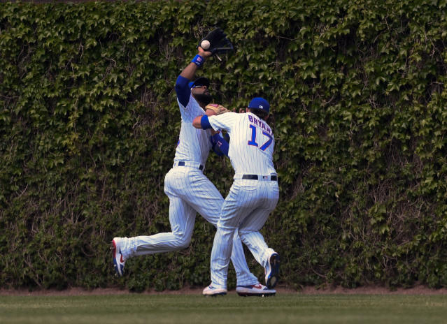 Chicago Cubs center fielder Jason Heyward, left, and right fielder Kris Bryant (17) collide while chasing a ball hit by Cincinnati Reds'c Eugenio Suarez (7) during the sixth inning of a baseball game Sunday, May 26, 2019, in Chicago. Bryant was charged with an error on the play. (AP Photo/Matt Marton)