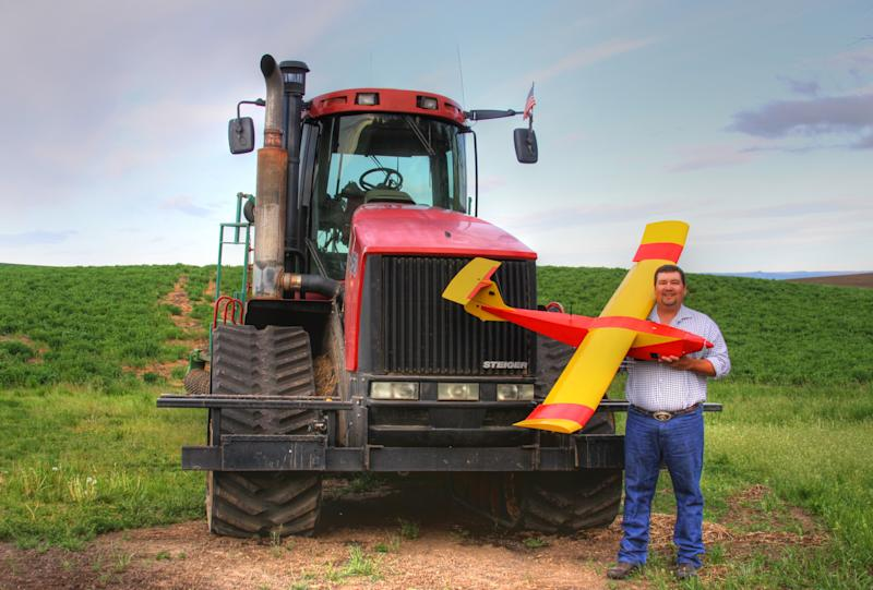 """In this May 2013 photo provided by Rhonda Blair, farmer Robert Blair stands in front of his tractor holding an unmanned aircraft that he built in Kendrick, Idaho. Blair uses the home-made drone equipped with up to four cameras to """"scout"""" his 1,500 acres of wheat, peas, barley and alfalfa and cow pasture. (AP Photo/Courtesy of Rhonda Blair)"""