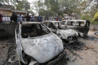 People look at cars that were vandalized during violence in New Delhi, India, Wednesday, Feb. 26, 2020. At least 20 people were killed in three days of clashes in New Delhi, with the death toll expected to rise as hospitals were overflowed with dozens of injured people, authorities said Wednesday. The clashes between Hindu mobs and Muslims protesting a contentious new citizenship law that fast-tracks naturalization for foreign-born religious minorities of all major faiths in South Asia except Islam escalated Tuesday. (AP Photo/Rajesh Kumar Singh)