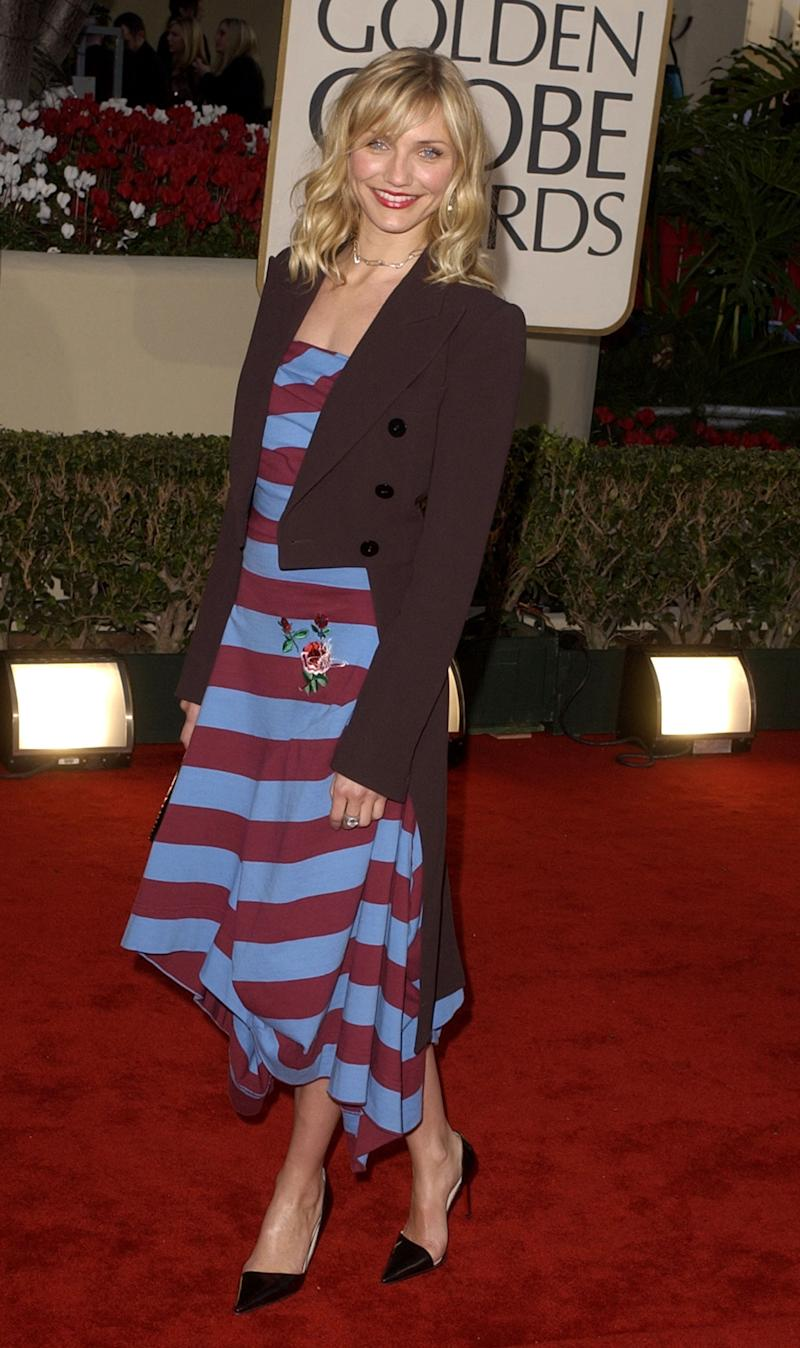 Diaz at the Golden Globe Awards wearing a Jean Paul Gaultier tuxedo jacket, Vivienne Westwood dress, Chrome Hearts diamond safety-pin necklace and earrings, Christian Louboutin pumps, and a vintage clutch (2002).