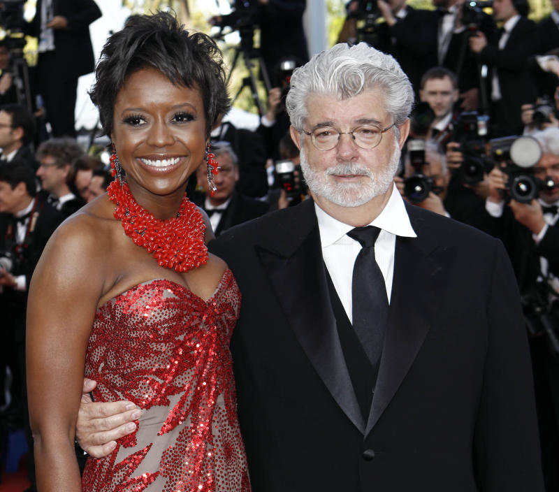 """In this May 14, 2010 photo, Filmmaker George Lucas, right, and Mellody Hobson arrive for the screening of """"Wall Street Money Never Sleeps"""", at the 63rd international film festival, in Cannes, southern France. A spokeswoman for Lucasfilm said on Thursday, Jan. 3, 2013, the 68-year-old director is engaged to 43-year-old investment firm president Mellody Hobson. (AP Photo/Matt Sayles, File)"""