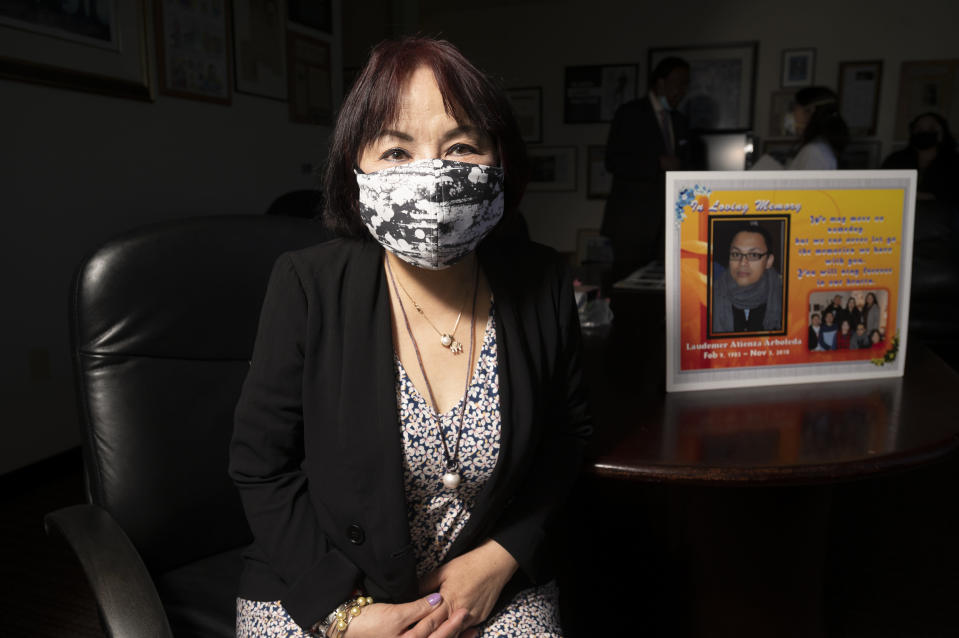 Jeannie Atienza sits with a picture of her son Laudemer Arboleda on Monday, May 3, 2021, in Oakland, Calif. Danville police officer Andrew Hall faces felony charges for shooting and killing Arboleda during a 2018 car chase. This and another fatal shooting by the same police officer in the wealthy San Francisco suburb have cast a spotlight on what criminal justice activists are calling a case of delayed justice and its deadly consequences. (AP Photo/Noah Berger)