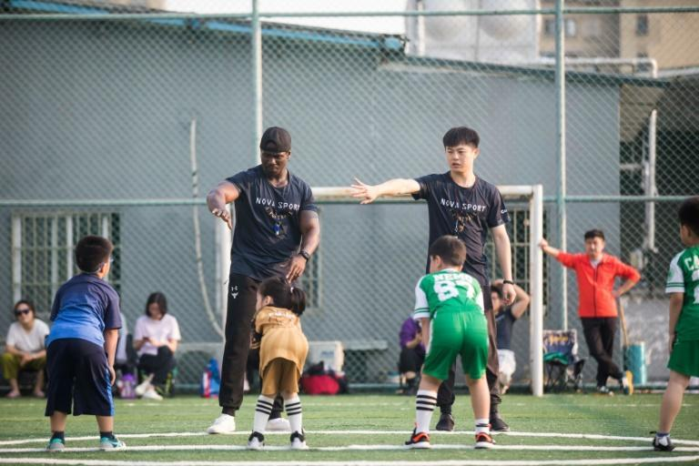 Coaches Paul Rene (left) and Chongwen Huang (right) put children through their paces at Hangzhou Clovers American Football Club, after parents got together to keep the club afloat after the owners allegedly made off with the money