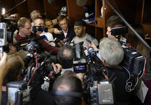 Indianapolis Colts running back Trent Richardson, top center, talks about joining the NFL team after being traded by the Cleveland Browns as he meets with the media in the locker room in Indianapolis, Thursday, Sept. 19, 2013. (AP Photo/Michael Conroy)