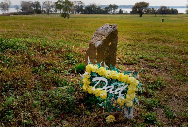"""Flowers left for a father, are seen at a grave marker in the Potter's field at Hart Island, October 25, 2019 in New York. - Elaine Joseph's baby daughter is one of around a million people buried in unmarked mass graves dug by prisoners on an eroding, once-off limits island in New York that's about to become more accessible. Since the late 1860s, unclaimed bodies, the poor, still-born children and AIDS victims have been laid to rest on the mile-long Hart Island, making it one of America's largest public cemeteries. Nicknamed """"the island of the dead,"""" access is heavily restricted. AFP attended the most recent of two escorted media trips a year while relatives can only visit on two days a month chosen by the prisons department. (Photo by Don Emmert / AFP) (Photo by DON EMMERT/AFP via Getty Images)"""