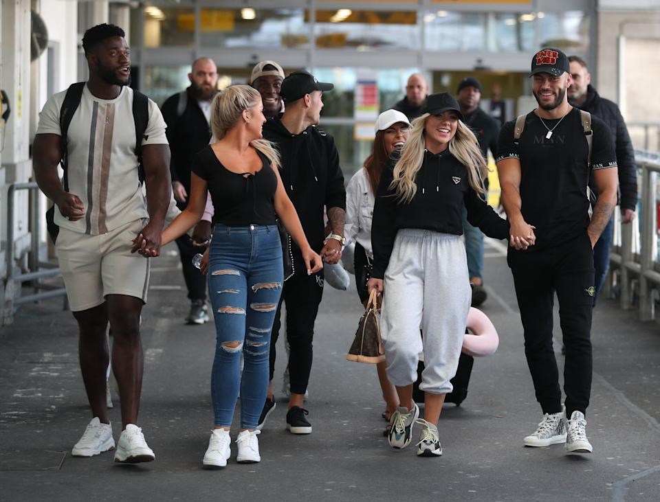 Love Island contestants (couples left to right) Jess Gale and Ched Uzor, Siannise Fudge and Luke Trotman (see rear partially hidden), Luke Mabbott and Demi Jones (centre) and winners Finley Tapp and Paige Turley, walk together after arriving at Heathrow Airport in London following the final of the reality TV show. (Photo by Andrew Matthews/PA Images via Getty Images)