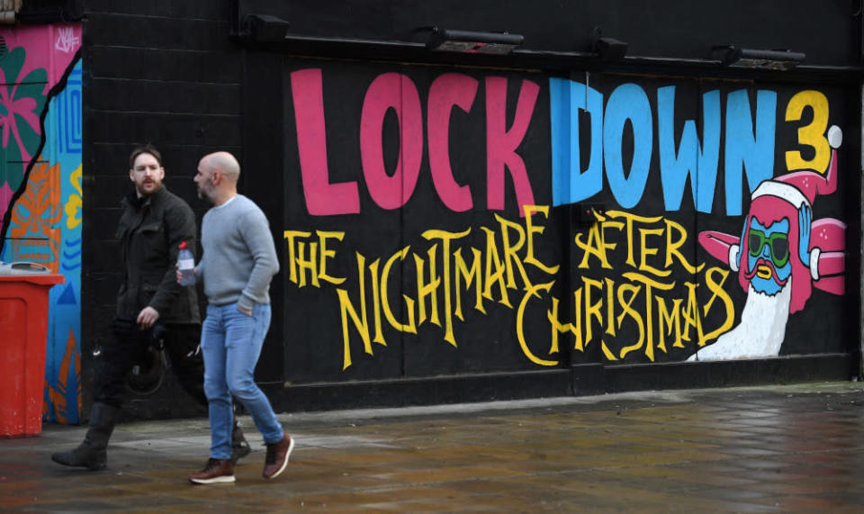 File picture shows pedestrians walking past graffiti reading 'Lockdown 3: The Nightmare after Christmas' painted on a boarded up restaurant in Manchester, England, February 15, 2021. — Reuters pic