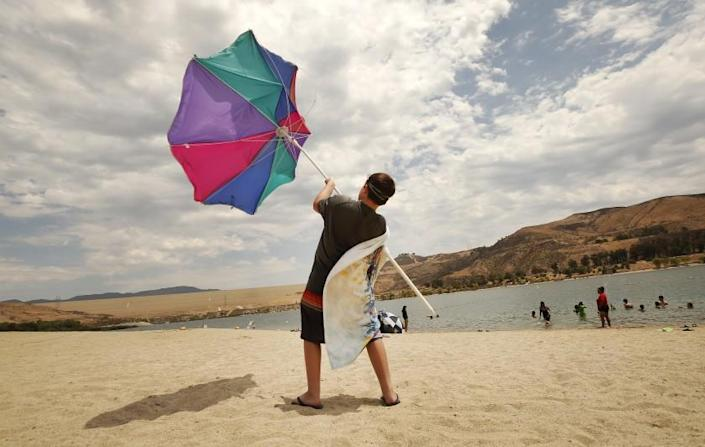 """CASTAIC, CA - JULY 08: Zachary Pruett, 10, catches wind with this umbrella as he was putting it away after he and his Mom Amanda Pruett, from Santa Clarita finish their morning at Castaic Lake Lagoon. The pair came to """"Cool off before the sun becomes dangerous."""" Said Amanda. Temperatures began to soar Thursday morning as a new heatwave is predicted to bring dangerously hot weather to California's inland regions this week, with relentlessly high temperatures that continue to torment the west coast. Castaic Lake Lagoon is now open daily 10am to 6pm. Castaic Lake Lagoon on Thursday, July 8, 2021 in Castaic, CA. (Al Seib / Los Angeles Times)."""