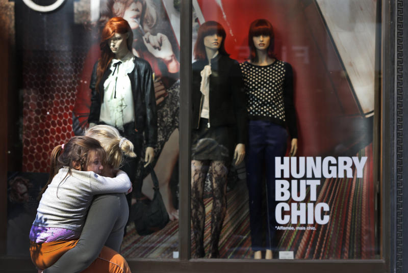 People walk past the window display of a department store in central Athens, Friday, Nov. 9, 2012. Cash-strapped Greece will issue short term debt on Tuesday in the hope of raising enough money to repay a key bond days later. Greece is not expected to get its next batch of international rescue loans by Nov. 16, when it has to roll over 5 billion euros in three-month treasury bills. (AP Photo/Lefteris Pitarakis)