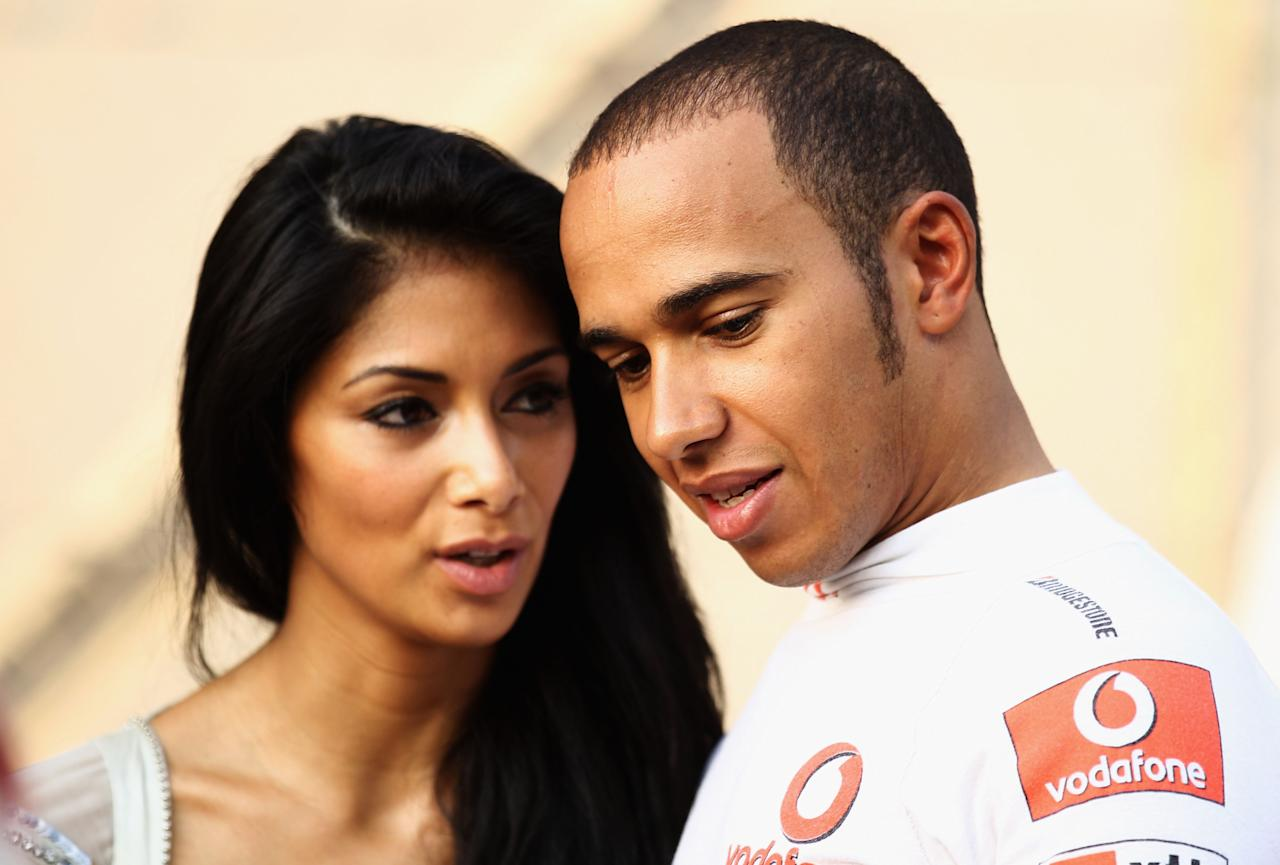ABU DHABI, UNITED ARAB EMIRATES - NOVEMBER 14:  Lewis Hamilton of Great Britain and McLaren Mercedes and his girlfriend Nicole Scherzinger of the Pussycat Dolls are seen on the grid before the Abu Dhabi Formula One Grand Prix at the Yas Marina Circuit on November 14, 2010 in Abu Dhabi, United Arab Emirates.  (Photo by Paul Gilham/Getty Images)