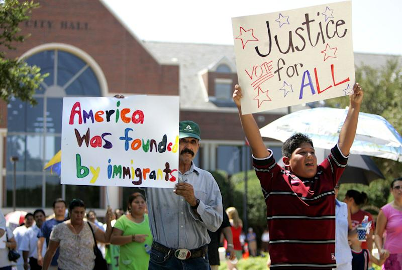 FILE - In this Aug. 26, 2006 file photo, Jerod Jaramillo, 12, right, and Jose Villaneda carry signs and march during an immigration law protest in front of city hall in Farmers Branch, Texas. The 5th U.S. Circuit Court of Appeals ruled Wednesday, March 21, 2012, that the ordinance passed by Farmers Branch in 2008 overstepped the town's authority, upholding a lower court ruling stopping a ban on illegal immigrants seeking housing. The law called on the city's building inspector to check the immigration status of anyone wanting to rent an apartment who wasn't a U.S. citizen. (AP Photo/L.M. Otero, File)