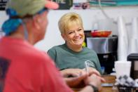 Lynn Martina, owner of Lynn's Quality Oysters in Eastpoint, Florida, U.S., talks to customers in her restaurant
