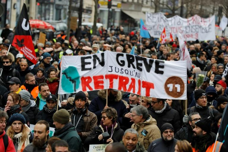"""Thousands of people gathered to demonstrate in central Paris against pension reform a month into the protest -- their banner reads """"on strike until withdrawal"""""""