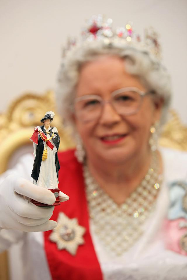 LONDON, ENGLAND - JANUARY 24:  A Queen Elizabeth II look-a-like holds a queen chess piece part of a 'Studio Anne Carlton' set commemorating the Queen's Diamond Jubilee at  the 2012 London Toy Fair at Olympia Exhibition Centre on January 24, 2012 in London, England. The annual fair which is organised by the British Toy and Hobby Association, brings together toy manufacturers with retailers from around the world.  (Photo by Oli Scarff/Getty Images)