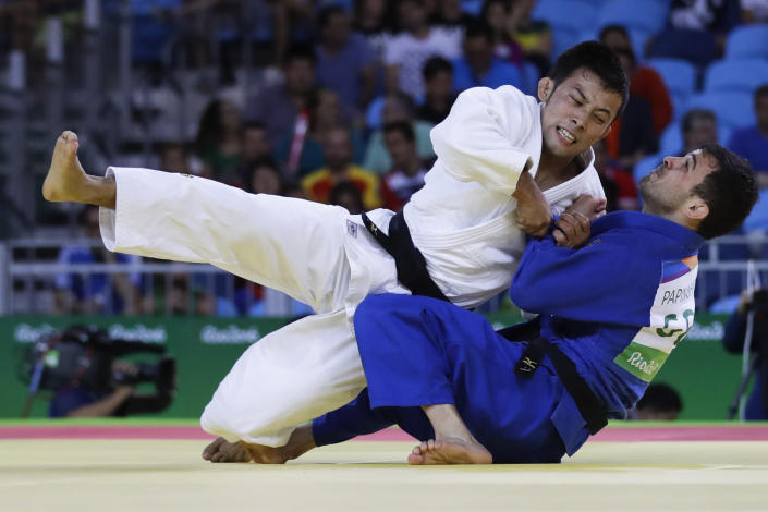 """FILE - In this Saturday, Aug. 6, 2016, file photo, Japan's Naohisa Takato, left, competes against Georgia's Amiran Papinashvili during the men's 60-kg judo competition at the 2016 Summer Olympics in Rio de Janeiro, Brazil. """"I had enough of the humiliating experience of ending up with a bronze medal in Rio,"""" Takato said. """"In the Tokyo Olympics, I'll definitely seize the gold. With whatever kind of judo, however unrefined that could be, I'll get a gold medal and play 'Kimigayo' (Japan's national anthem) in the awarding ceremony."""" (AP Photo/Markus Schreiber, File)"""