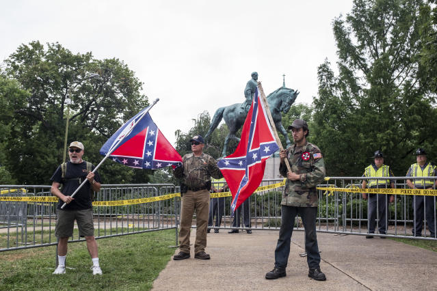 <p>Men hold confederate flags in front of a statue of Robert E. Lee at Emancipation park prior to the Unite the Right Rally on August 12, 2017 in Charlottesville, Virginia. (Photo: Jason Andrew/Getty Images) </p>